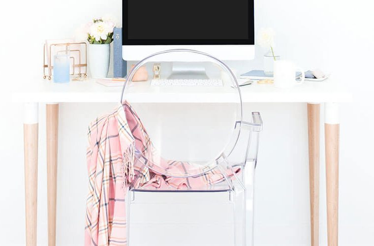 white desktop with mac computer and clear chair in front of desk