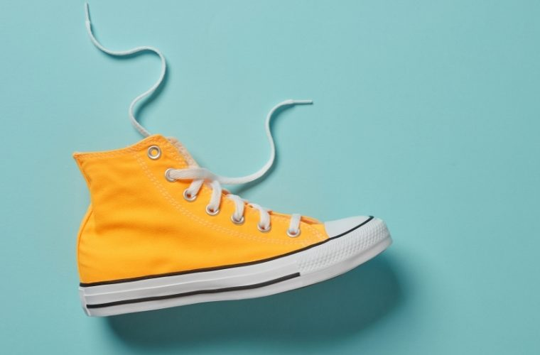 yellow high top canvas shoe with blue background
